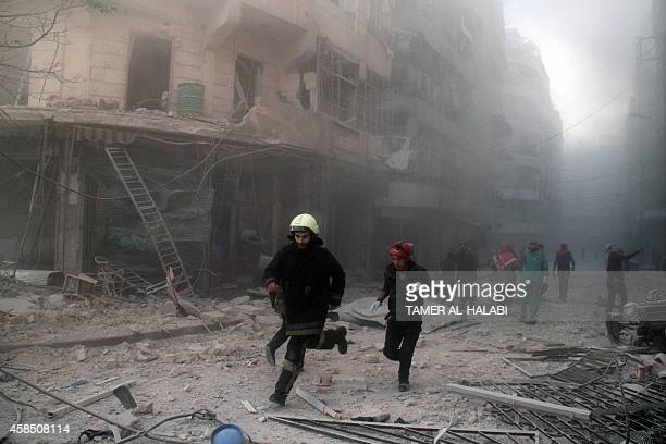 Emergency responders rush following a reported barrel bomb attack by government forces in the AlMuasalat area in the northern Syrian city of Aleppo...