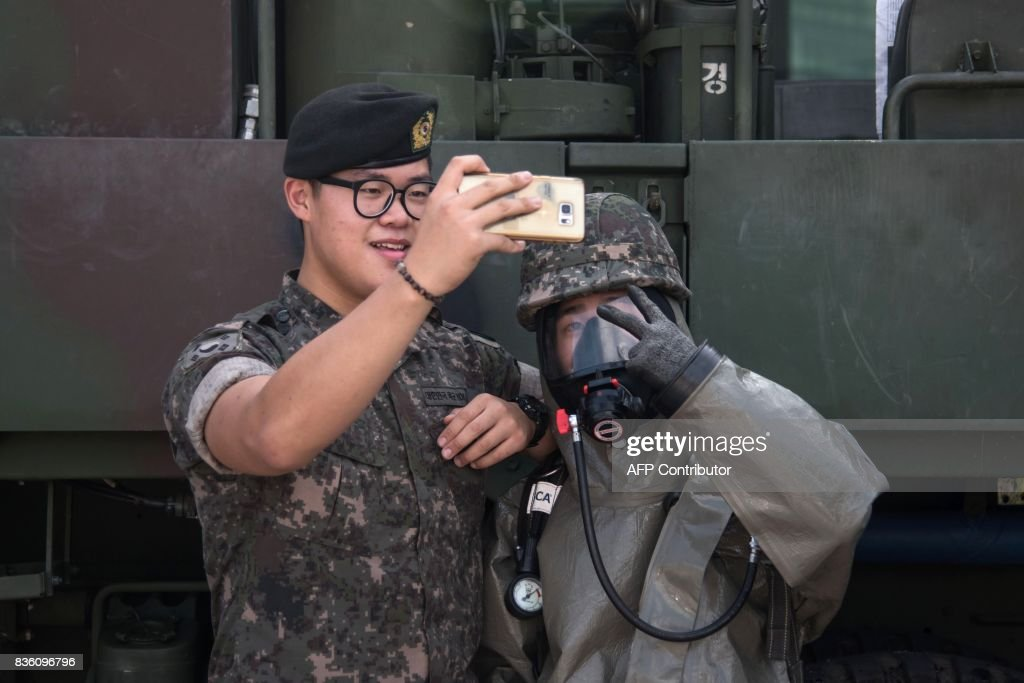 Emergency service members take a selfie prior to an anti-terror drill in Goyang on August 21, 2017. Meanwhile tens of thousands of South Korean and US troops are taking part in the 'Ulchi Freedom Guardian' joint military drills, a largely computer-simulated exercise that runs for two weeks in the South. / AFP PHOTO / Ed JONES