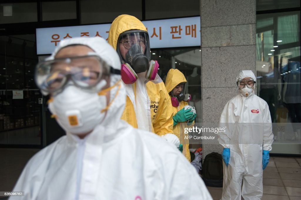 Emergency service members wearing bio-hazard suits take part in an anti-terror drill in Goyang on August 21, 2017. Meanwhile tens of thousands of South Korean and US troops are taking part in the 'Ulchi Freedom Guardian' joint military drills, a largely computer-simulated exercise that runs for two weeks in the South. / AFP PHOTO / Ed JONES