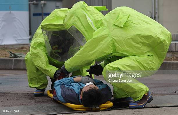 Emergency service personnel wearing chemical protective clothing participate in a chemical incident exercise on April 16 2013 in Seoul South Korea...