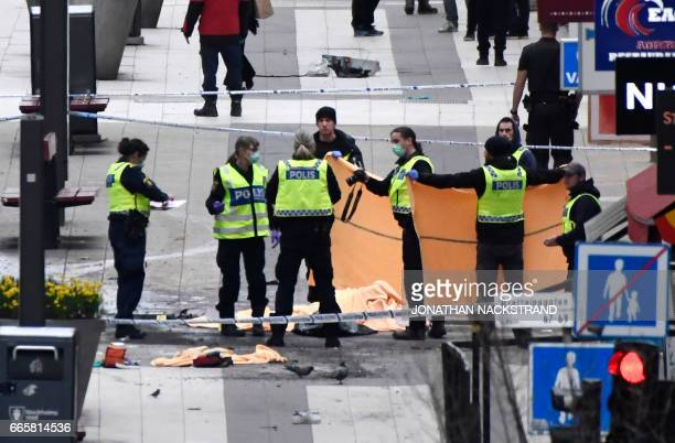 Emergency services and police work at the scene where a truck crashed into the Ahlens department store at Drottninggatan in central Stockholm April 7...