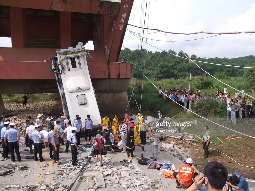 Emergency services attend the scene of a bus accident after it plunged from the collapsed Wuyishan Gongguan Bridge on July 14, 2011 in Wuyishan, Fujian province of China. One person was killed and 22 injured in the incident. The cause of the Bridge collapse is not as yet known.