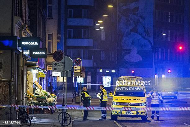 Emergency services personnel stand behind a police cordon on February 15 close to Norrebro station after the alleged offender of a terrorist attack...