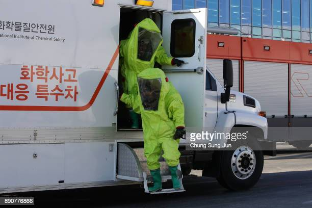 Emergency services personnel wearing protective clothing participate in an antiterror drill at the Olympic Staduim venue of the Opening and Closing...