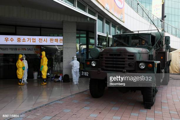Emergency services personnel wearing protective clothing stand next to a military vehicle during a simulated chemical terrorism crisis as part of an...
