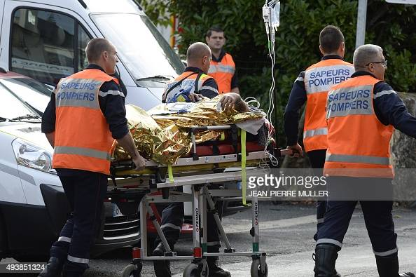 Emergency services personnle take away an injured person from the site of a collision on October 23 2015 in Puisseguin near Libourne southwestern...