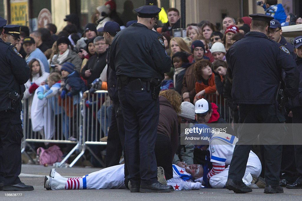 Emergency services rush to attend to a man dressed as a clown who collapsed during the 86th Annual Macy's Thanksgiving Day Parade on November 22, 2012 in New York City. Macy's donated tickets and transportation to this year's Thanksgiving Day Parade to 5,000 people from neighborhoods hardest hit by Superstorm Sandy.