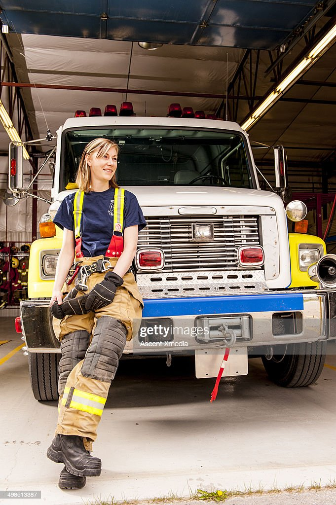 Emergency services worker sits on fire truck grill