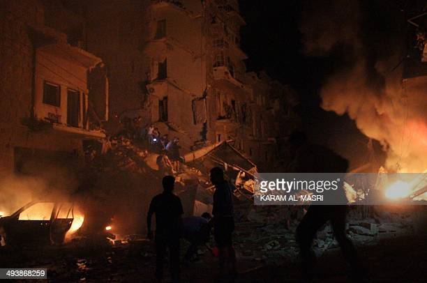 Emergency teams extinguish flames following a reported barrelbomb attack on the northern Syrian city of Aleppo on May 26 2014 Aleppo was once Syria's...