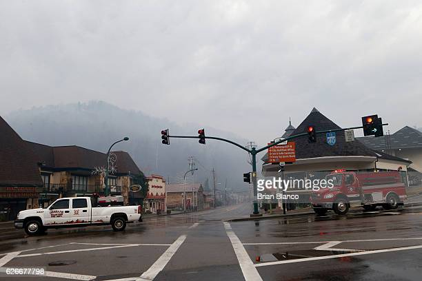 Emergency vehicles drive the streets as smoke fills the air and surrounds businesses and resorts in the wake of a wildfire November 30 2016 in...
