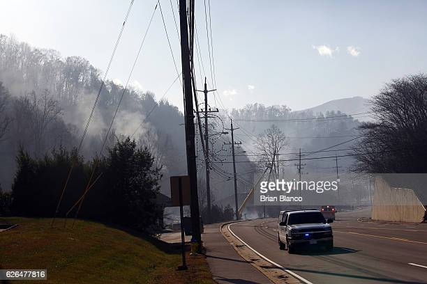 Emergency vehicles race by the remains of businesses and homes as they smolder after a wildfire November 29 2016 in Gatlinburg Tennessee Thousands of...
