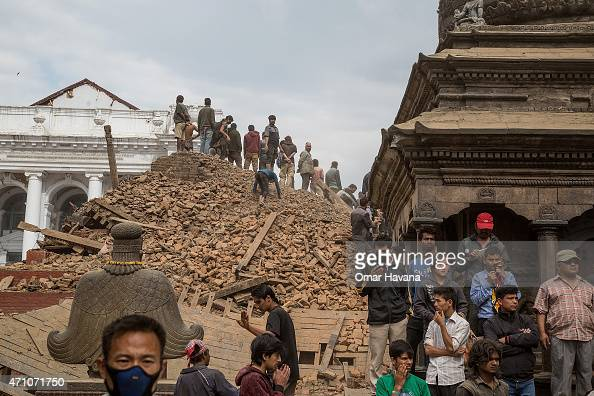 Emergency workers and bystanders clear debris while searching for survivors under a collapsed temple in Basantapur Durbar Square following an...