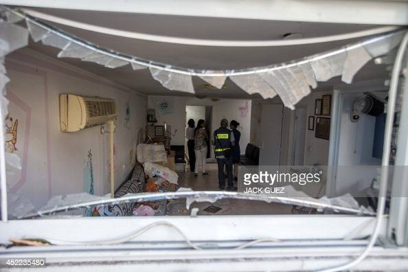 Emergency workers and Israeli security check a house damaged by a rocket fired by militants from the Gaza Strip on July 16 in the city of Ashkelon...