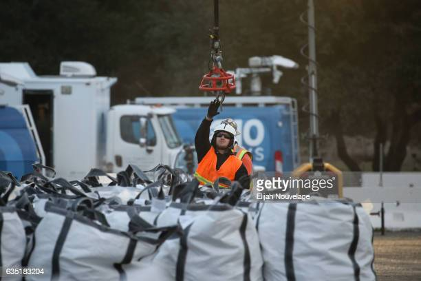 Emergency workers attach a bag of rocks to a helicopter as work continues to fix the erosion damage below the emergency spillway at Oroville Lake on...