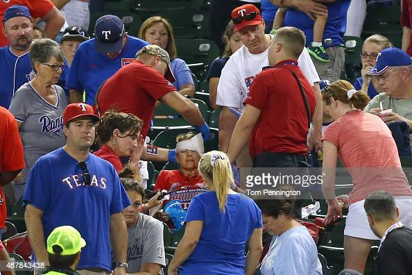 Emergency workers attend to a fan that was hit by a foul ball as the Texas Rangers take on the Oakland Athletics at Globe Life Park in Arlington on...