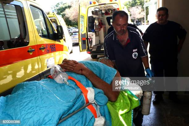 Emergency workers attend to a person injured in an earthquake on the Greek island of Kos as they arrive for treatment on the island of Crete in...