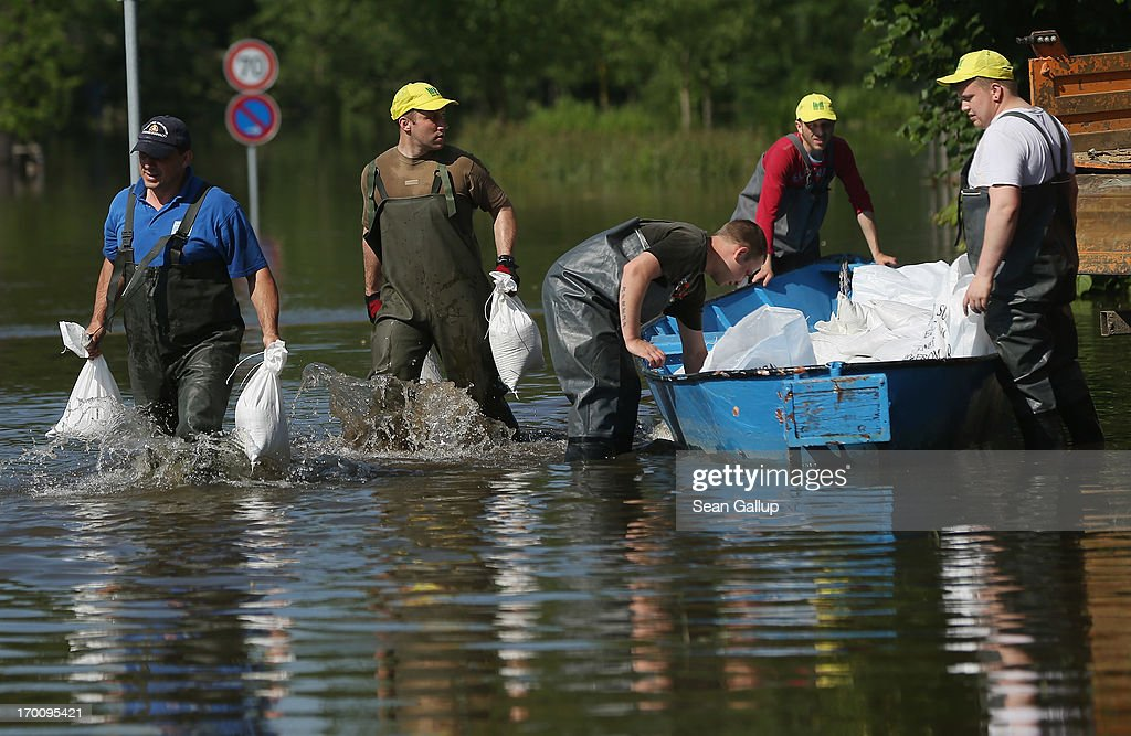 Emergency workers carry sandbags through floodwaters from the swollen Elbe river to protect a nearby water pumping station on June 7, 2013 in Coswig, Germany. Floodwaters that have devastated parts of Saxony and Thuringia are now moving north, threatening towns along the Elbe and Saale rivers all the way to Hamburg. Eastern and southern Germany are suffering under floods that in some cases are the worst in 400 years. At least four people are dead and tens of thousands have evacuated their homes.