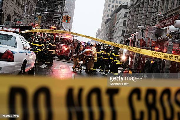 Emergency workers converge at the scene of a collapsed crane in a roadway in lower Manhattan Friday morning on February 5 2016 in New York City The...