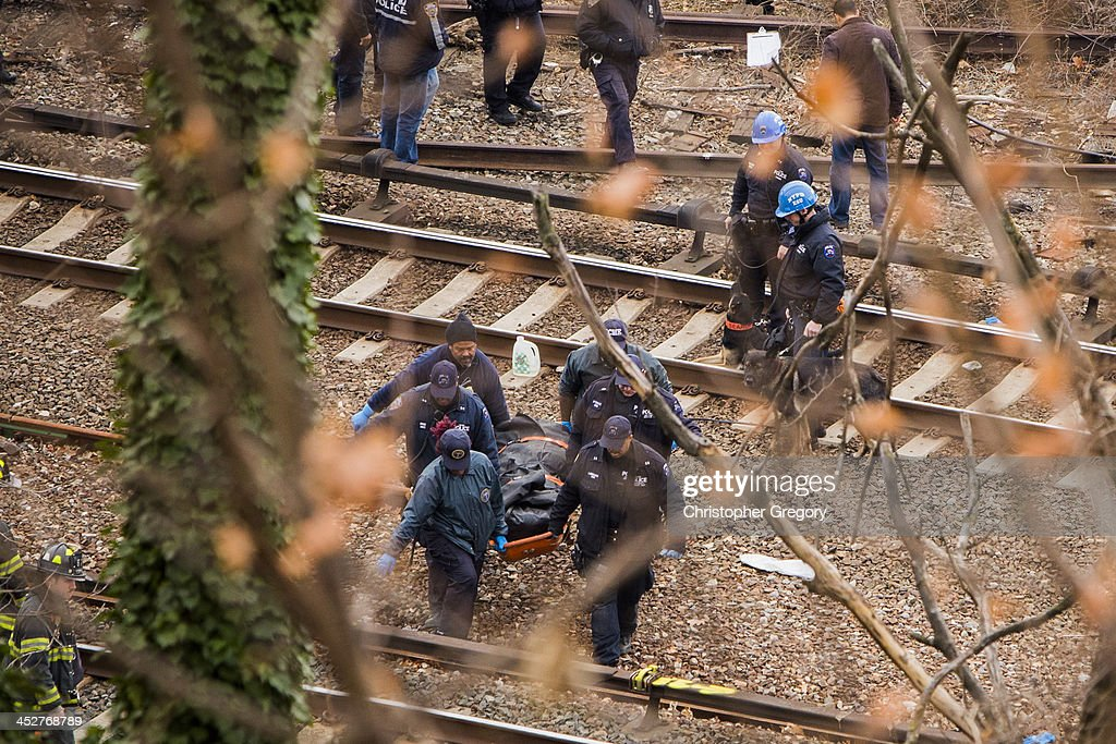 Emergency workers remove a dead body from the scene after a Metro-North commuter train derailed just north of the Spuyten Duyvil station December 1, 2013 in the Bronx borough of New York City. Multiple injuries and at least 4 deaths were reported after the seven car train left the tracks as it was heading to Grand Central Terminal along the Hudson River line.