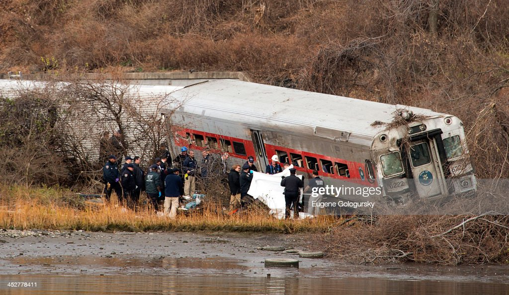 Emergency workers respond to the scene of a Metro-North commuter train derailment just north of the Spuyten Duyvil station December 1, 2013 in the Bronx borough of New York City. Multiple injuries and at least 4 deaths were reported after the seven car train left the tracks as it was heading to Grand Central Terminal along the Hudson River line.