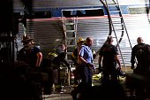 Emergency workers search for the injured after an Amtrak passenger train carrying more than 200 passengers from Washington DC to New York derailed...