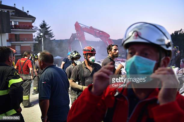 Emergency workers search the rubble of a building that was destroyed during an earthquake on August 25 2016 in Amatrice Italy The death toll in the...