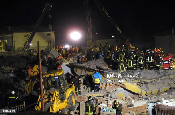 Emergency workers search the rubble of a collapsed school following an earthquake November 1 2002 in San Giuliano di Puglia in south central Italy A...