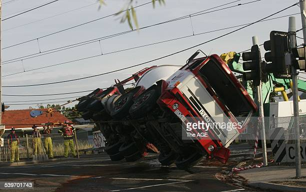 Emergency workers toil to remove an overturned concrete mixer truck from the level crossing on Grange road Alphington on 20th December 2005 THE AGE...