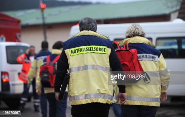 Emergency workers walk at the scene of a fire at a house with a workshop for handicapped people in Titisee Neustadt southern Germany on November 26...