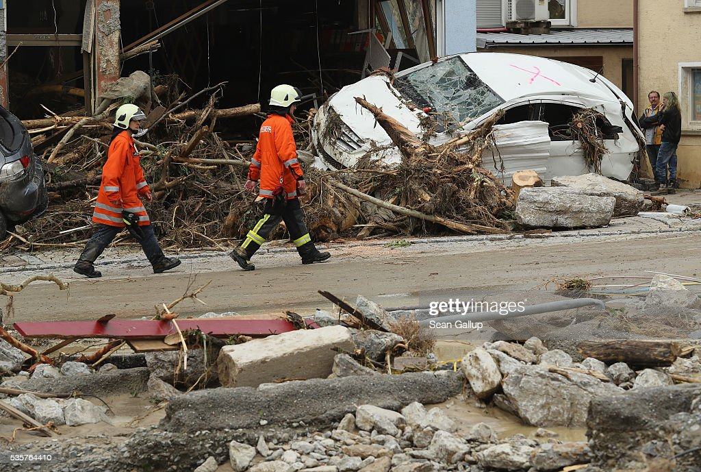 Emergency workers walk past a car smashed against a building in the village center following a furious flash flood the night before on May 30, 2016 in Braunsbach, Germany. The flood tore through Braunsbach, crushing cars, ripping corners of houses and flooding homes during a storm that hit southwestern Germany. Miraculously no one in Braunsbach was killed, though three people died as a result of the storm in other parts of the country.