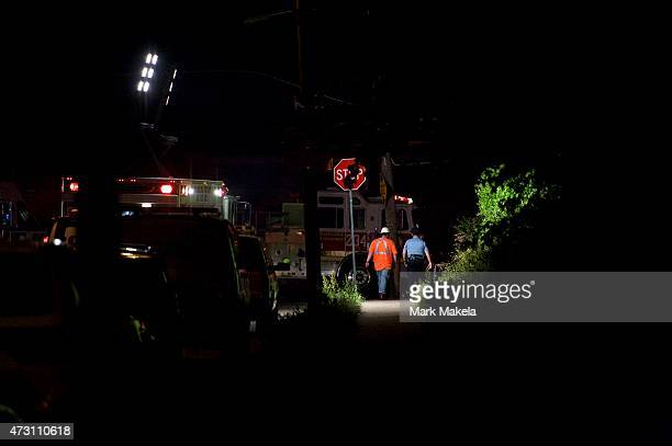 Emergency workers walk towards the wreckage of an Amtrak passenger train that derailed carrying more than 200 passengers from Washington DC to New...