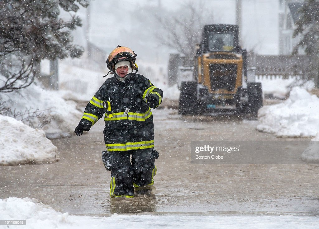 Emergency workers walked through knee deep water along Annapolis Way on Plum Island as a large winter storm hit the region, causing flooding during high tide.