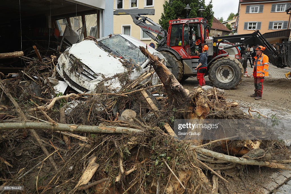 Emergency workersstand near a car smashed against a building in the village center following a furious flash flood the night before on May 30, 2016 in Braunsbach, Germany. The flood tore through Braunsbach, crushing cars, ripping corners of houses and flooding homes during a storm that hit southwestern Germany. Miraculously no one in Braunsbach was killed, though three people died as a result of the storm in other parts of the country.