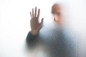 Emerging man behind glass