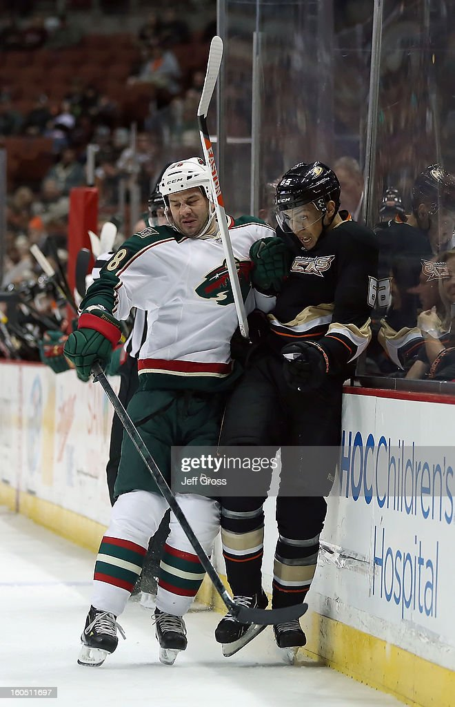 <a gi-track='captionPersonalityLinkClicked' href=/galleries/search?phrase=Emerson+Etem&family=editorial&specificpeople=6365314 ng-click='$event.stopPropagation()'>Emerson Etem</a> #65 of the Anaheim Ducks is checked into the boards by <a gi-track='captionPersonalityLinkClicked' href=/galleries/search?phrase=Zenon+Konopka&family=editorial&specificpeople=2105876 ng-click='$event.stopPropagation()'>Zenon Konopka</a> #28 of the Minnesota Wild in the first period at Honda Center on February 1, 2013 in Anaheim, California. The Ducks defeated the Wild 3-1.
