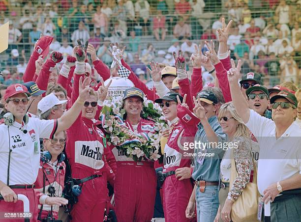 Emerson Fittipaldi of Brazil driver of the Team Penske Penske PC22 Chevrolet 265C V8t celebrates with his team members after winning the PPG CART...