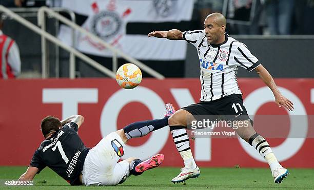 Emerson of Corinthians fights for the ball with Julio Buffarini of San Lorenzo during a match between Corinthians and San Lorenzo as part of Group 2...