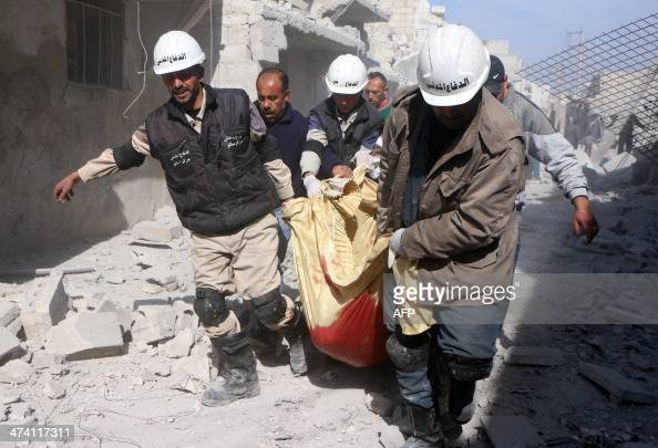 Emgergency response members carry a body following an air strike attack by government forces on the northern Syrian city of Aleppo on February 22...