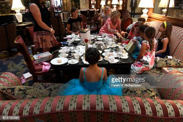 Emi {cq} Harrington dressed up in a blue princess dress to attend a 6th birthday party and tea for her friend Nora Stiles opening bag at right in the...