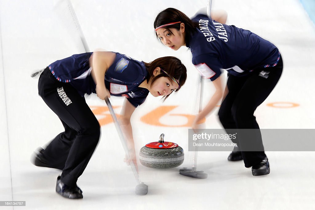 Emi Shimizu (R) and Chiaki Matsumura (L) of Japan sweep in the match between Japan and Russia on Day 5 of the Titlis Glacier Mountain World Women's Curling Championship at the Volvo Sports Centre on March 20, 2013 in Riga, Latvia.