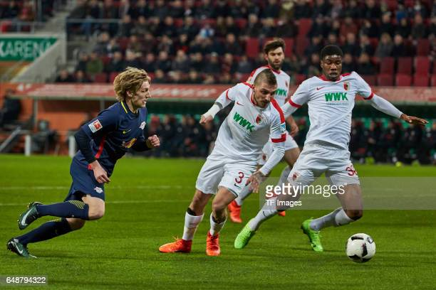 Emil Forsberg of Leipzig and Konstantinos Stafylidis of Augsburg and Kevin Danso of Augsburg battle for the ball during the Bundesliga match between...
