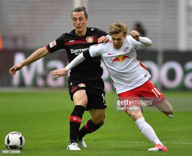 Emil Forsberg of Leipzig is challenged by Julian Baumgartlinger of Leverkusen during the Bundesliga match between RB Leipzig and Bayer 04 Leverkusen...