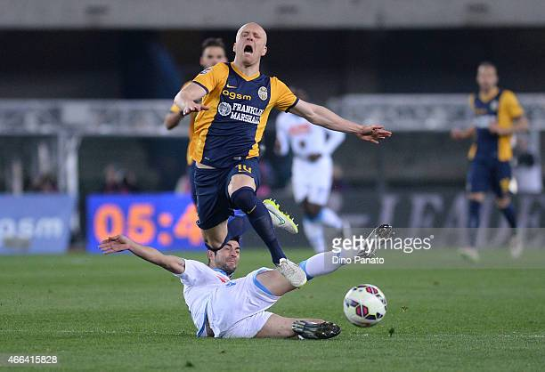 Emil Hallfredsson of Hellas Verona is tackled to Giandomenico Mesto of SSC Napoli during the Serie A match between Hellas Verona FC and SSC Napoli at...