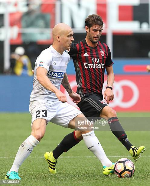Emil Hallfredsson of Udinese Calcio is challenged by Andrea Poli of AC Milan during the Serie A match between AC Milan and Udinese Calcio at Stadio...
