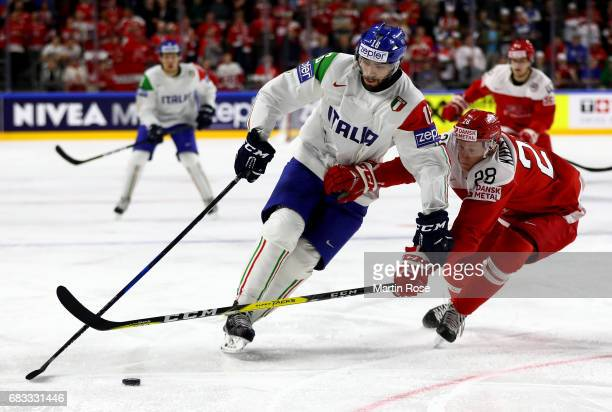 Emil Kristensen of Denmark challenges Giovanni Morini of Italy for the puck during the 2017 IIHF Ice Hockey World Championship game between Denmark...