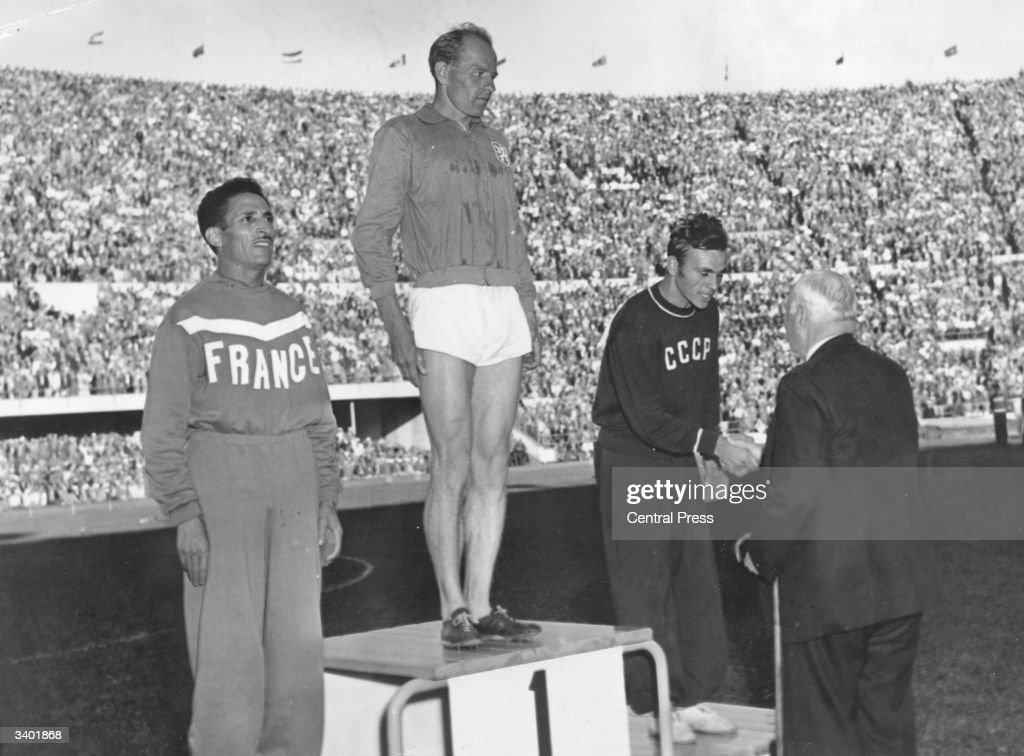 Emil Zatopek (1922 - 2000) of Czechoslovakia, receives his gold medal at the 1952 Helsinki Olympics after winning the 10,000 metres. Alain Mimoun of France and Alexander Anufriev came second and third respectively.