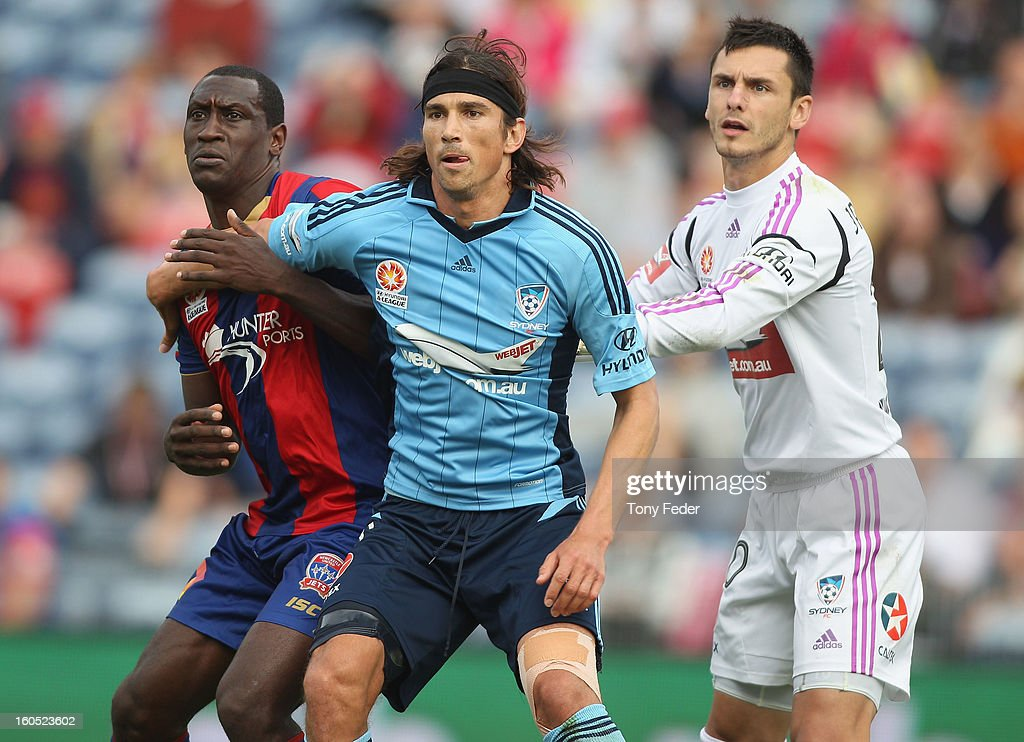 Emile Heskey of the Jets (L) and Adam Griffiths of Sydney (C) jostle in the golamouth with Sydney goalkeeper Vedran Janjetovic during the round 19 A-League match between the Newcastle Jets and Sydney FC at Hunter Stadium on February 2, 2013 in Newcastle, Australia.