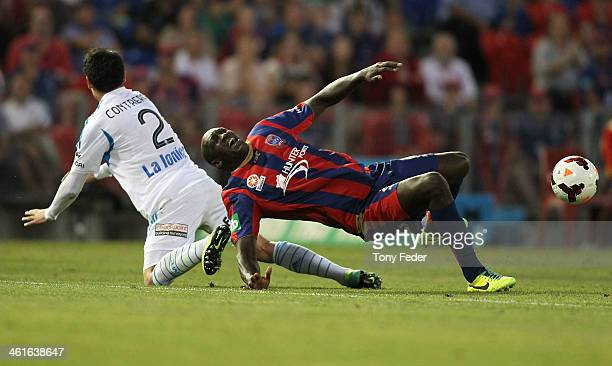 Emile Heskey of the Jets avoids a sliding tackle from Pablo Contreras of the Victory during the round 14 ALeague match between the Newcastle Jets and...