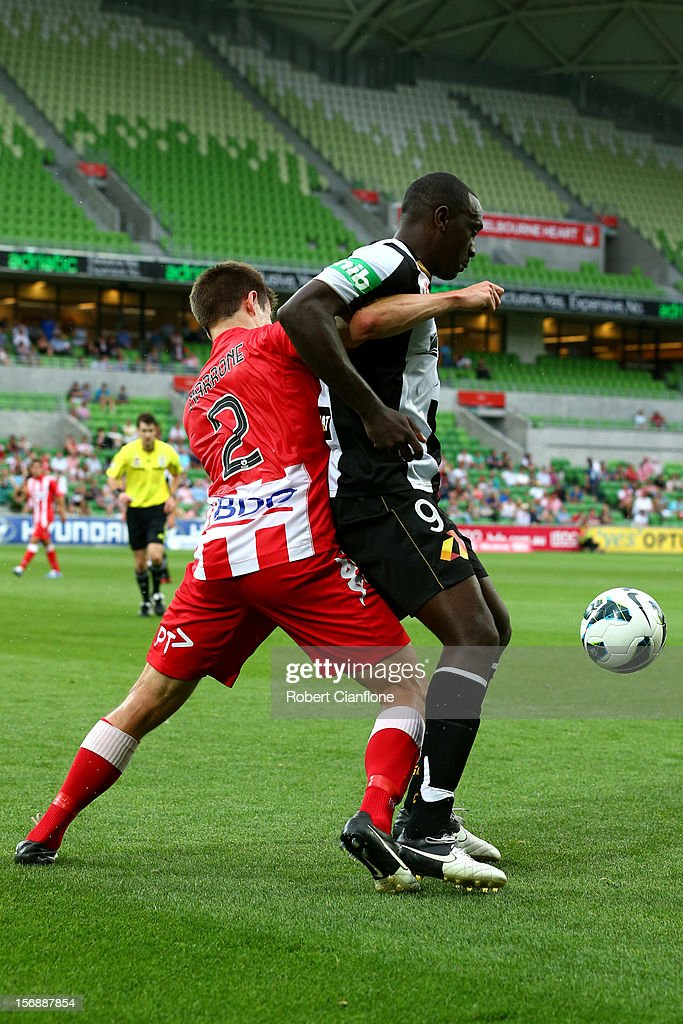 Emile Heskey of the Jets is challenged for the ball by Michael Marrone of the Heart during the round eight A-League match between the Melbourne Heart and the Newcastle Jets at AAMI Park on November 24, 2012 in Melbourne, Australia.