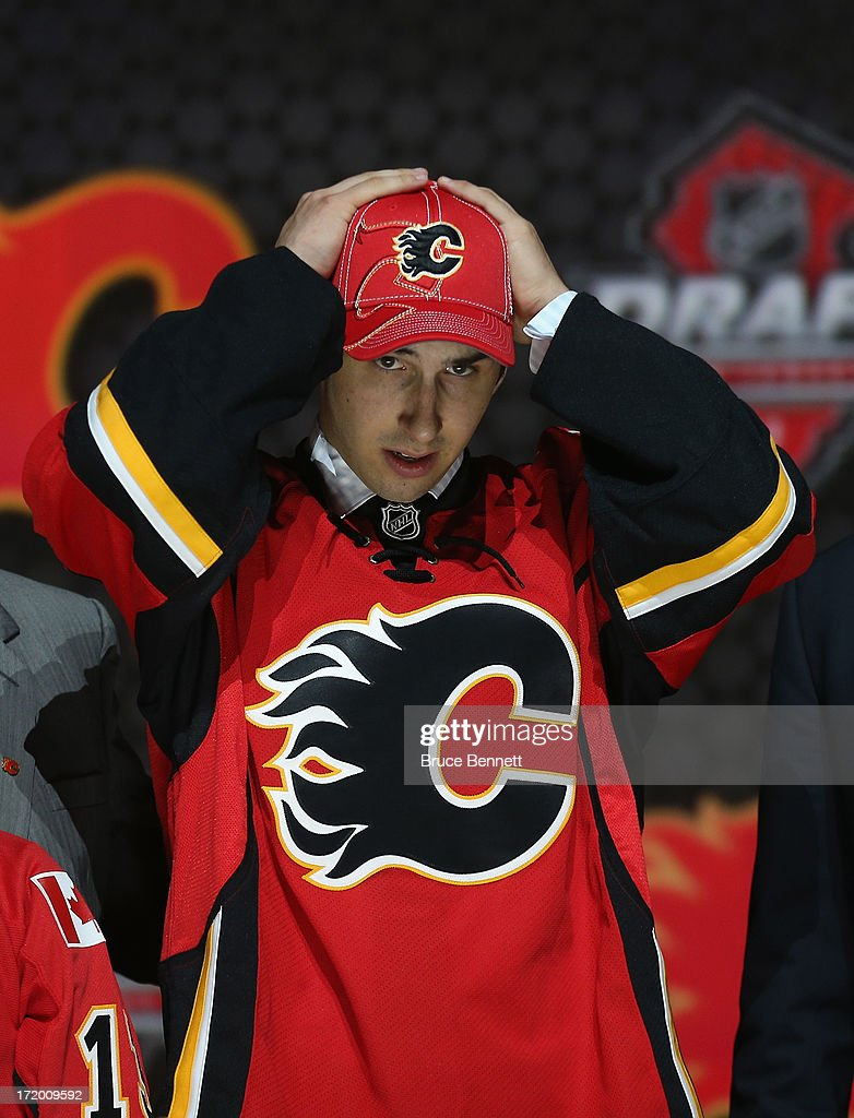 Emile Poirier of Canada, adjusts his Calgary Flames hat on stage after he was drafted #22 overall in the first round by Calgary during the 2013 NHL Draft at the Prudential Center on June 30, 2013 in Newark, New Jersey.